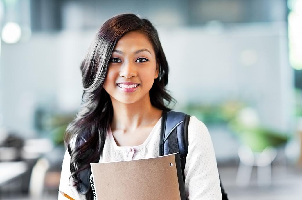 Un adolescente sonriente usando una mochila y llevando sus cuadernos