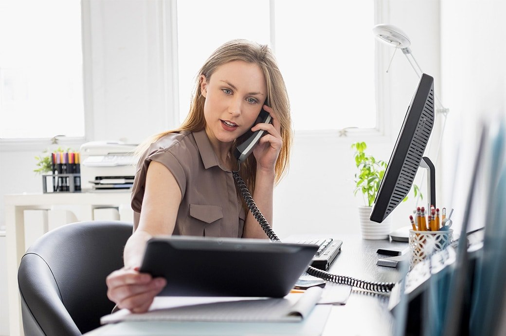 Una mujer en el escritorio de su oficina mirando una tablet mientras esta en el telefono