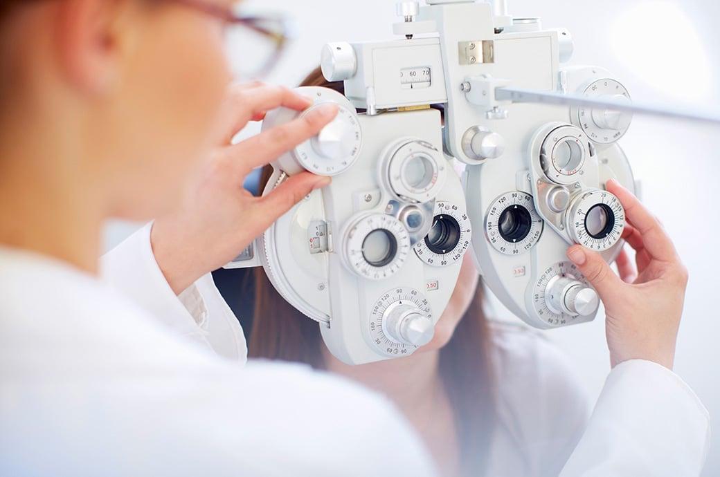 Una mujer joven detrás de un foróptero mientras el doctor revisa sus ojos durante un examen ocular